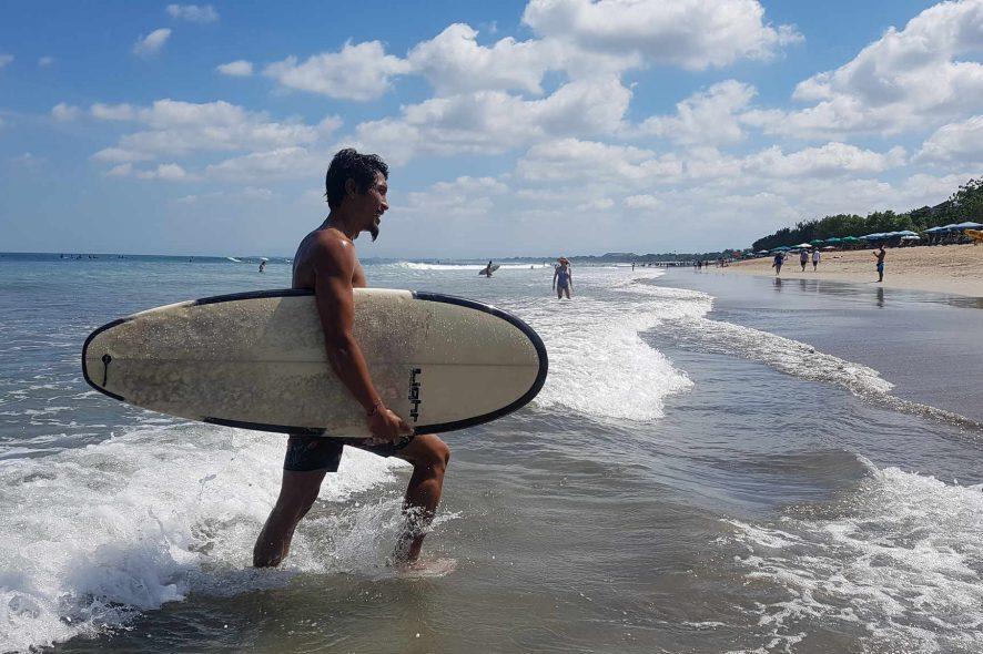 Surfista a sair do mar com a prancha de surf debaixo do braço em Bali
