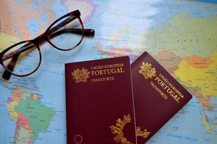 dois passaportes portugueses em cima de um mapa do mundo e com uns óculos ao lado