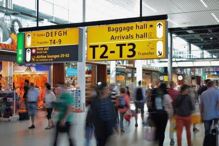 Interior do terminal do Aeroporto de Aesterdão cheio de pessoas a caminhar. Foto de Pexels