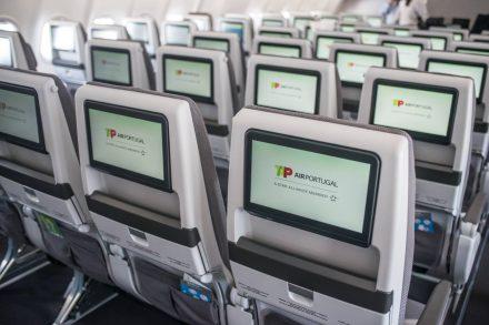 Interior de um A330 Neo da TAP com ecrãs individuais de entretenimento de passageiros