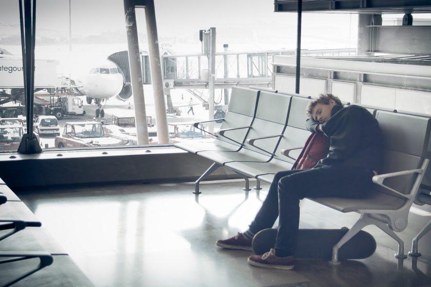 Homem dorme sentado numa sala de espera do aeroporto.