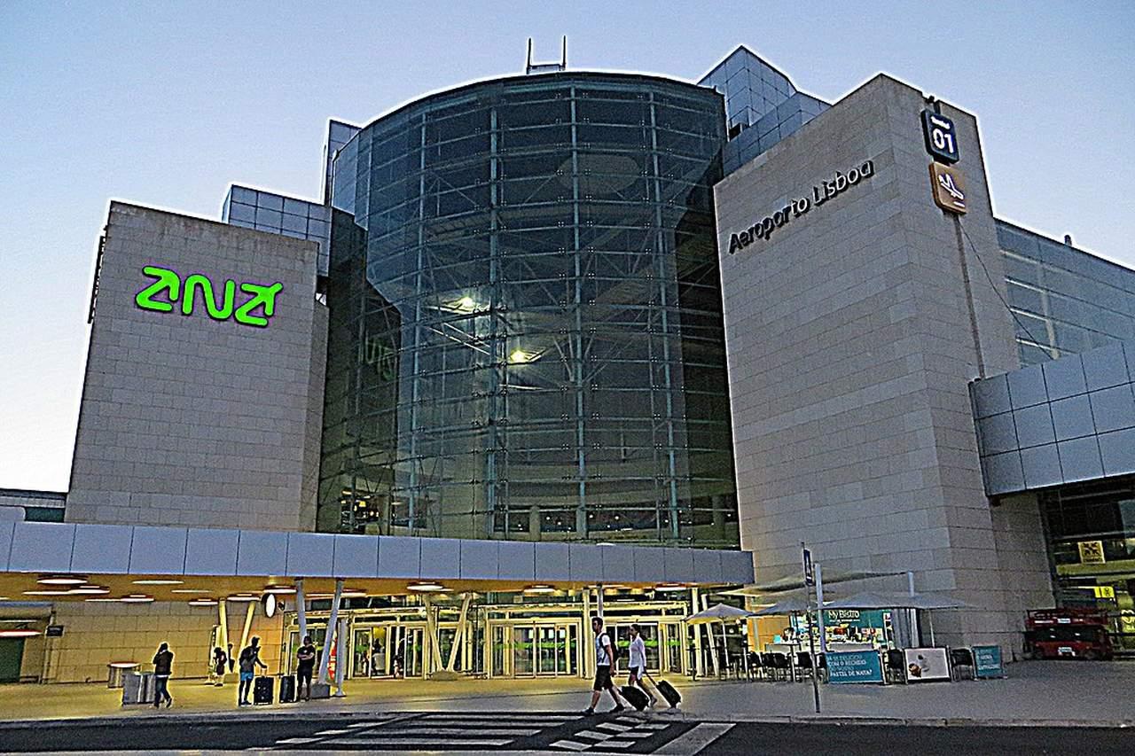 Fachada do aeroporto de Lisboa ao final da tarde com o logotipo da ANA Aeroportos de Portugal iluminado
