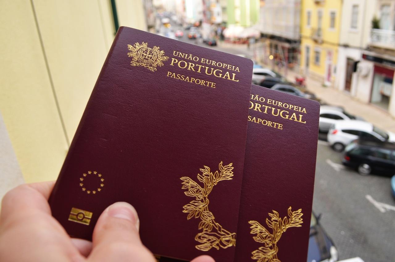 dois passaportes portugueses erguidos sobre uma rua de Lisboa Foto de Cláudia Paiva