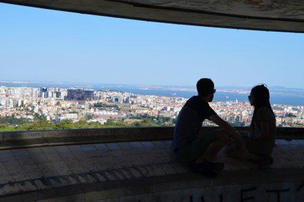 Dois turistas sentados no Miradouro Panorâmico de Monsanto a observar a cidade de Lisboa