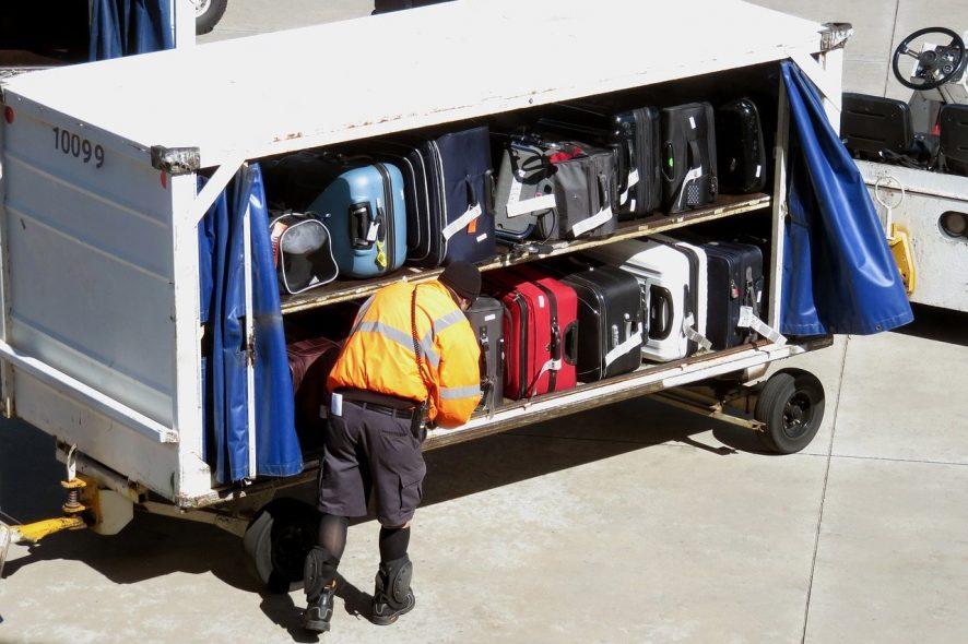 Funcionário acomoda malas de viagem num carrinho de transporte no aeroporto