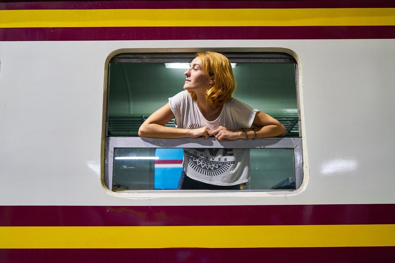 Mulher com a cabeça fora da janela de um comboio enquanta viaja. Foto de Pixabay