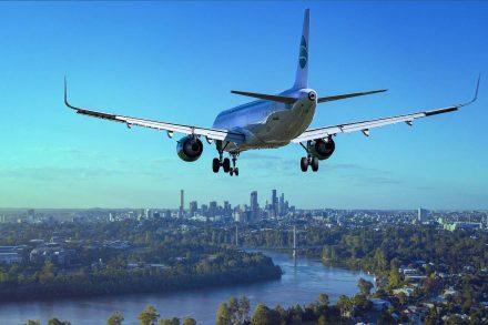Avião em aproximação para aterragem a sobrevoar uma cidade com o trem de aterragem em baixo. Foto de Pixabay