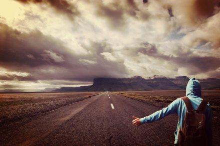 Viajante solitário de mochila às costas a pedir boleia numa estrada deserta foto de pixabay