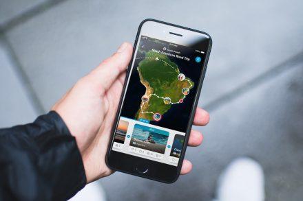 Aplicação Polarsteps no ecrã de um iPhone segurado pela mão de um utilizador. Foto de Polarsteps
