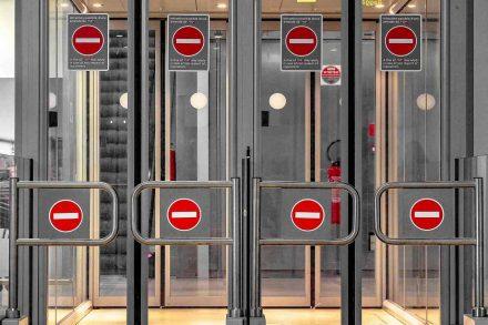 Cancelas de segurança fechadas no aeroporto com o sinais se sentido proibido. Imagem por djedj na Pixabay