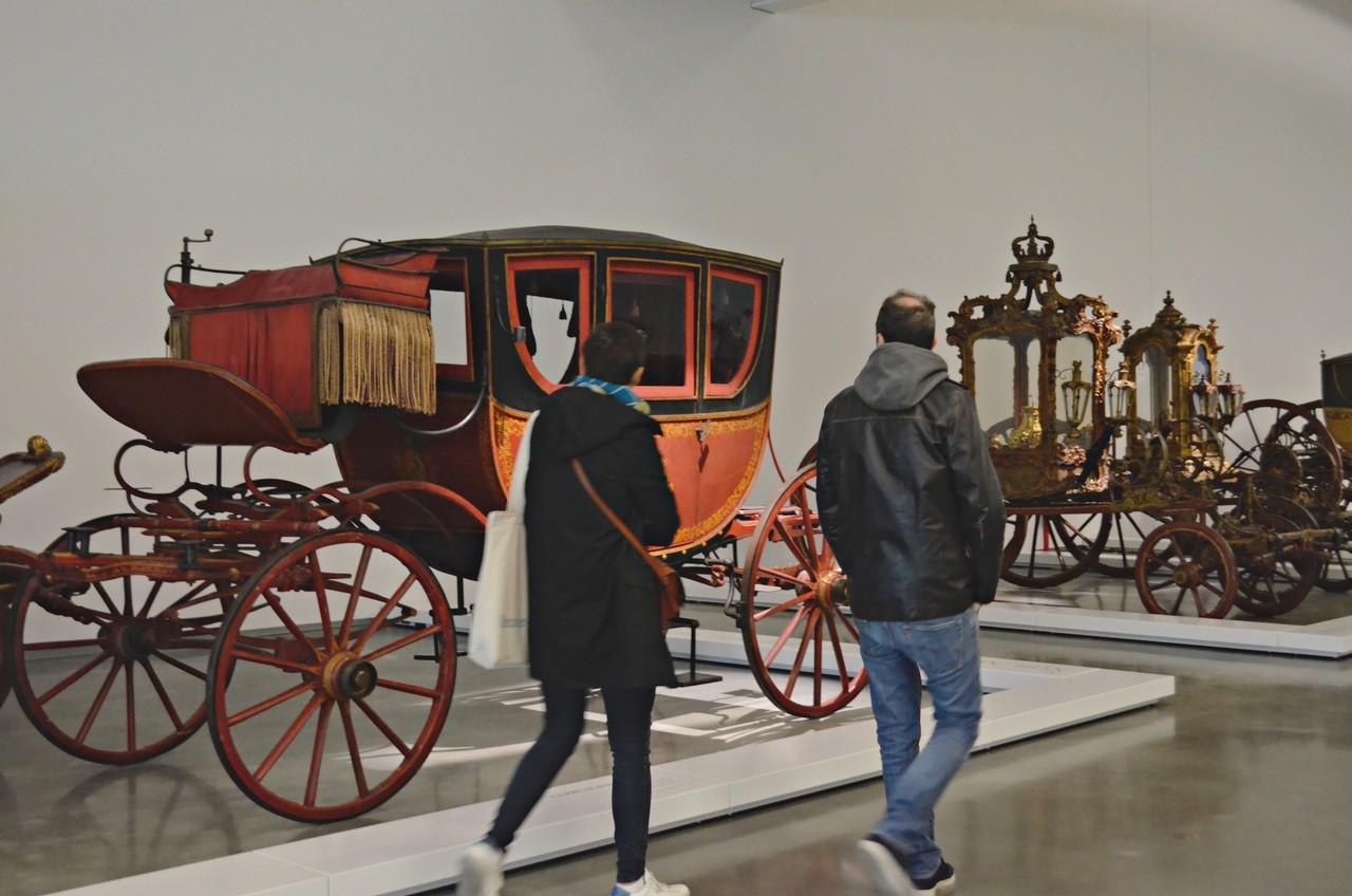 Dois visitantes a observarem a exposição permanente do Museu dos Coches de Belém, em Lisboa. Foto de Cláudia Paiva