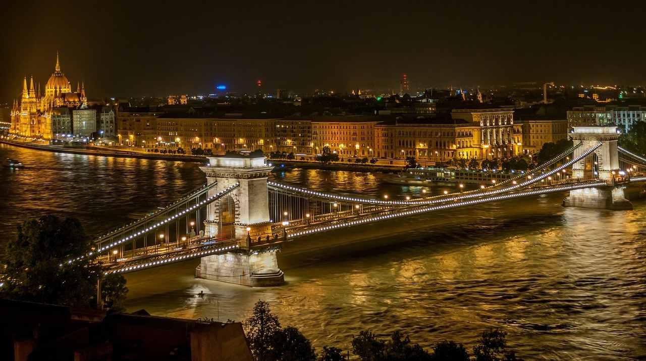 Foto panorâmica de Budapeste à noite, na Hungria, onde se vê a ponte sobre o rio. Foto de Pixabay
