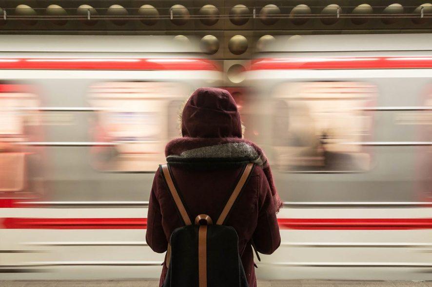 Mulher de costas, com mochila e gorro na cabeça numa estação de comboio. Foto de Pixabay