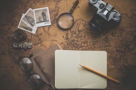 Óculos, blócos de notas, fotografias, lupa e câmara fotográfica pousadas em cima de um mapa do mundo antigo. Foto de PIxabay