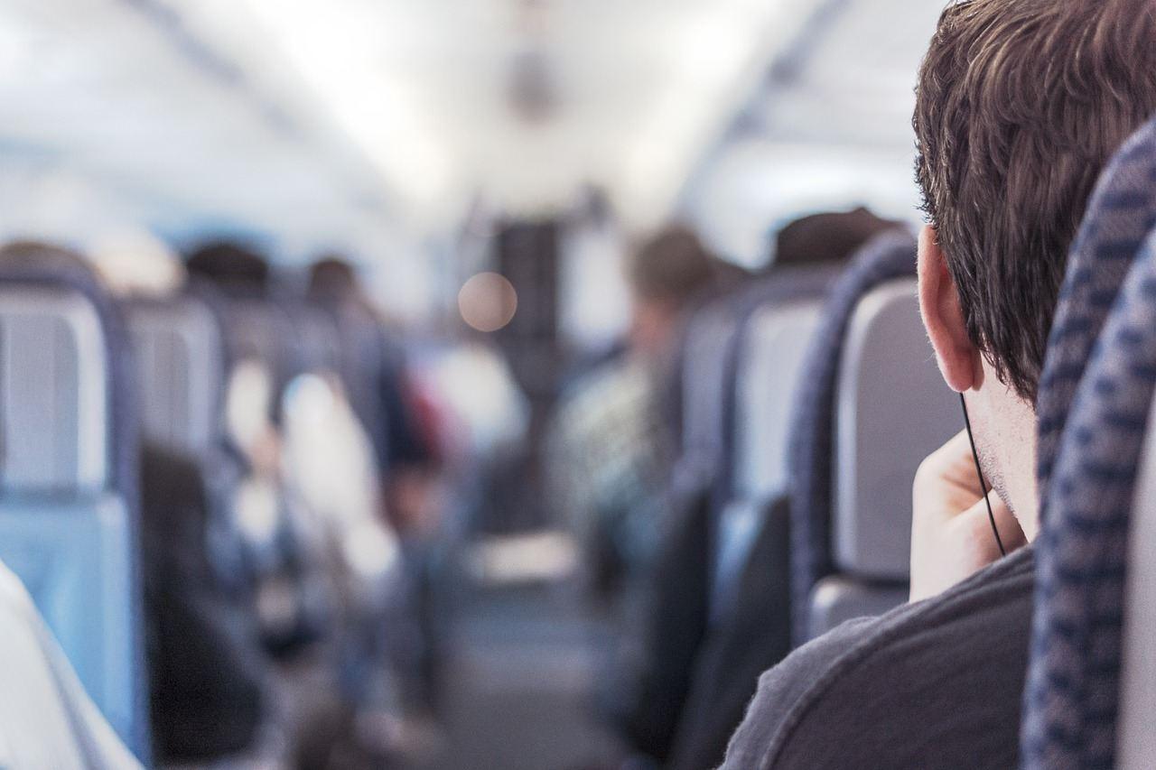 Passageiro, de costas, a viajar dentro de um avião comercial e a usar headphones nos ouvidos. Foto de Pixabay