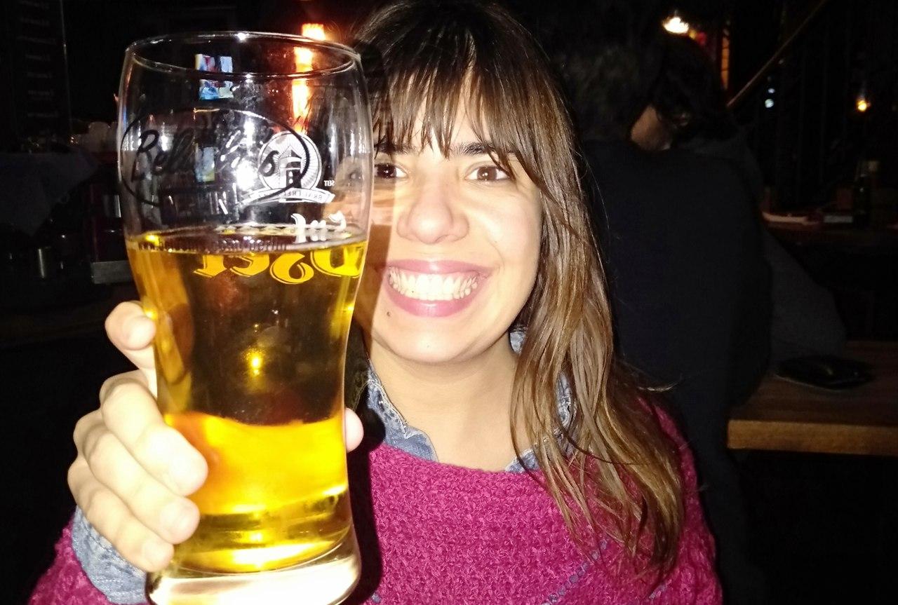 Rapariga (Sara Reis) sorridente com copo de cerveja alemã na mão em jeito de brinde. Foto de Sara Reis