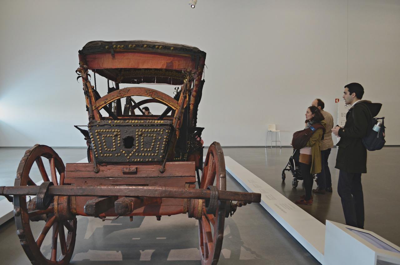 Visitantes a observarem um dos coches expostos no Museu dos Coches de Belém, em Lisboa. Foto de Cláudia Paiva