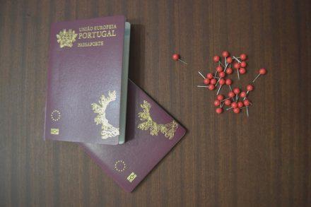 dois passaportes portugueses em cima de uma mesa com pioneses vermelhos ao lado. Foto de Cláudia Paiva