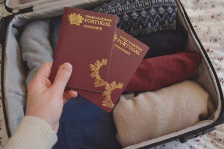 dois passaportes portugueses erguido sobre uma mala de viagem com roupa. Foto de Cláudia Paiva
