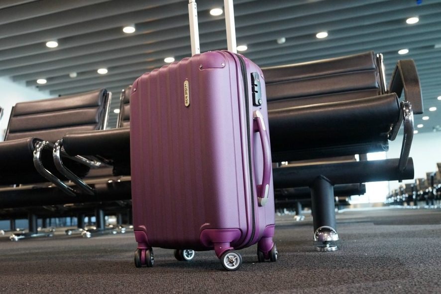 mala de cabine de viagem lilás num aeroporto. Foto de Pixabay
