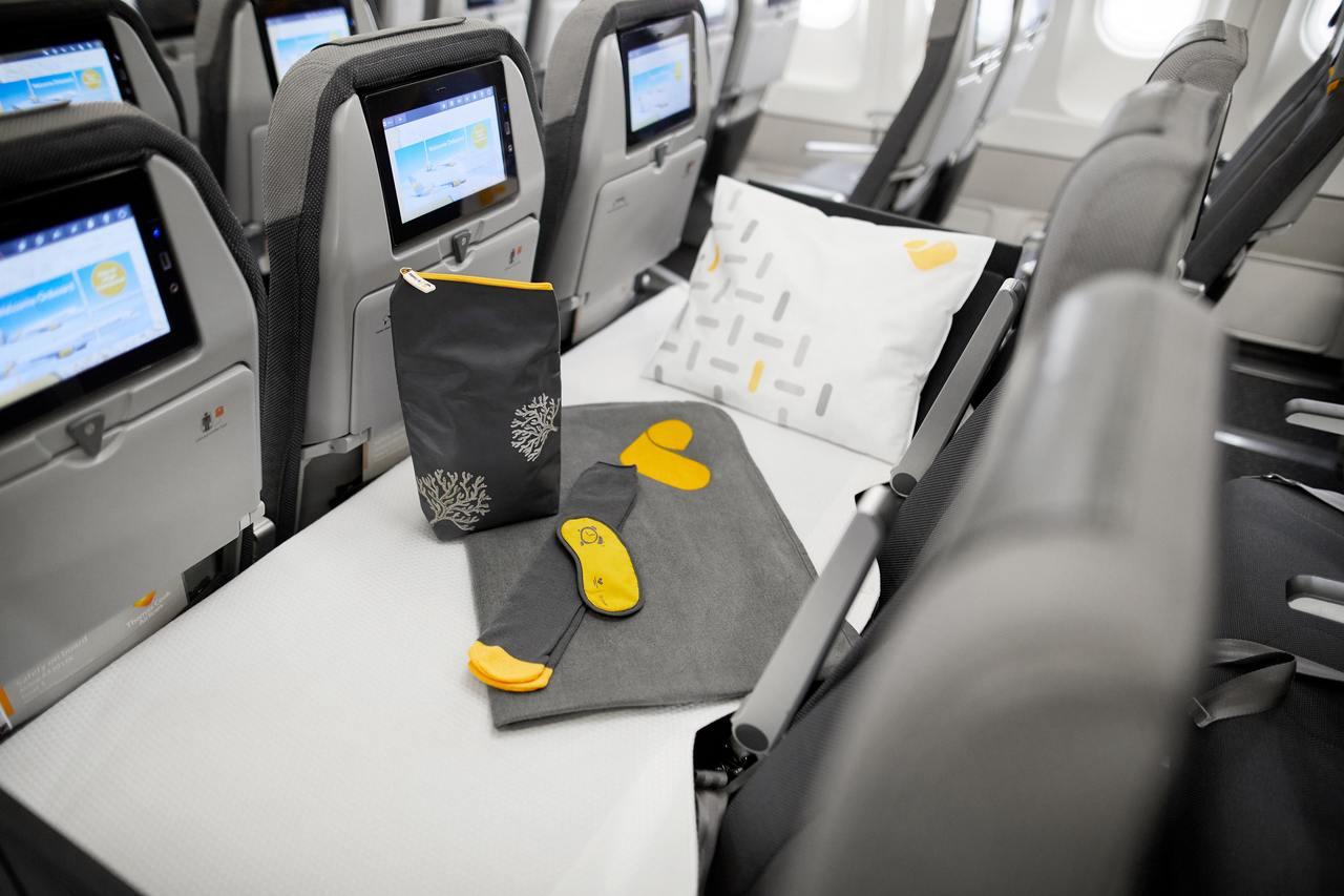 Assentos da classe económica de um avião da Thomas Cook Airlines transformados em cama, com lençol, almofada e kit de produtos de higiene