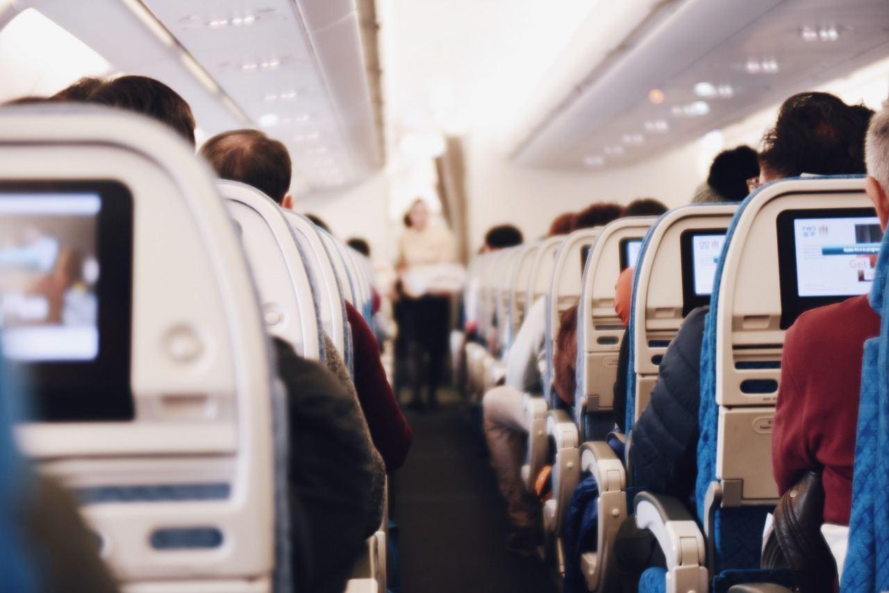 Cabine de passageiros de um avião comercial com ecrãs de entretenimento