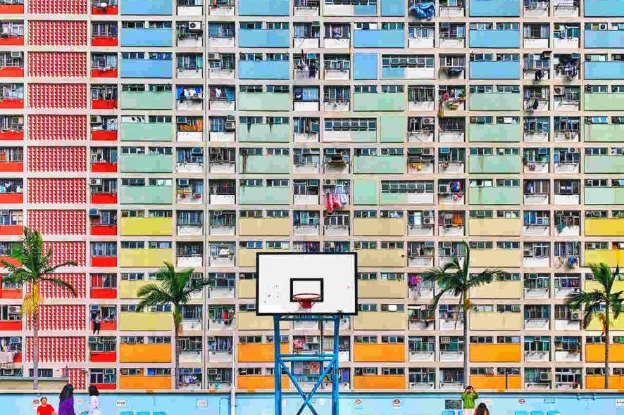 Cesto de basquetebol com prédio colorido em fundo. Foto de Alex Jiang Apple