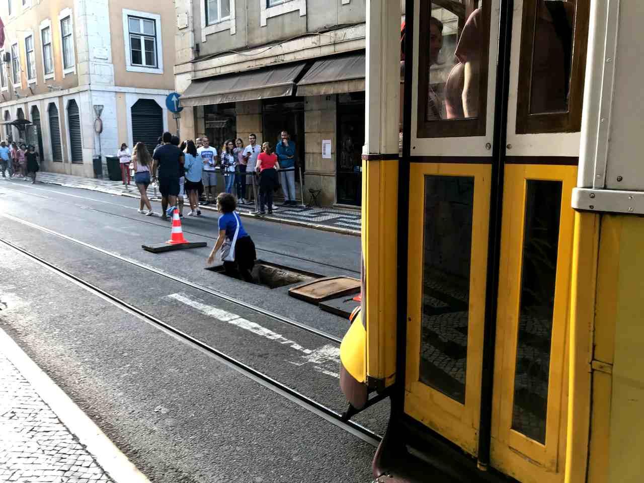 Elétrico a passar na Rua da Conceição, em Lisboa, enquanto uma senhora sai das Galerias Romanas pelo alçapão