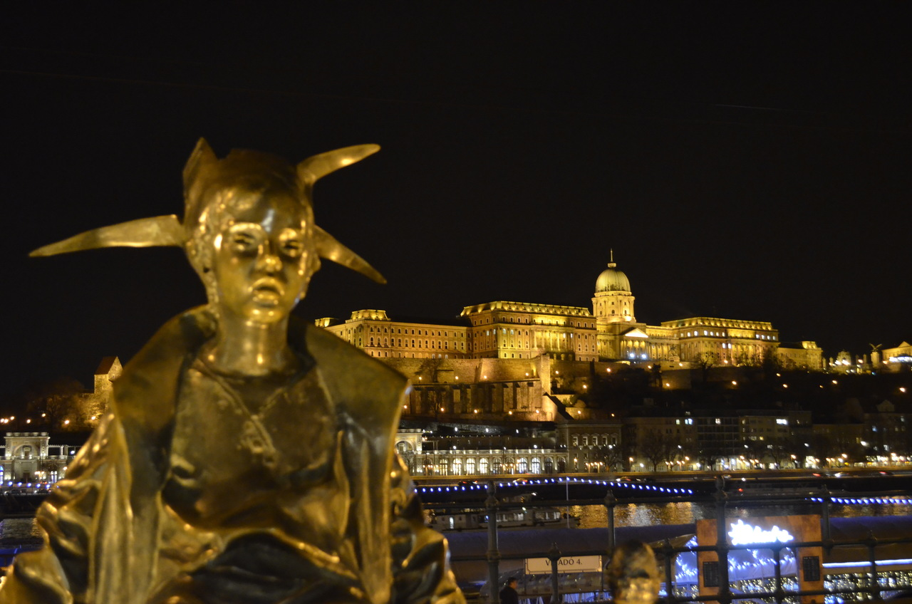 Estátua da Pequena Princesa com o Castelo de budapeste em fundo, iluminado durante a noite