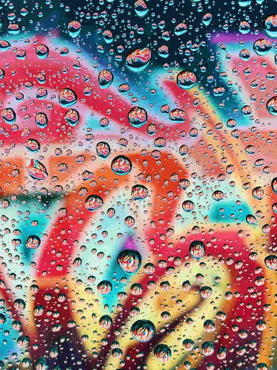 Gotas de água num vidro com fundo colorido de grafiti. Foto de Andrew Griswold Apple