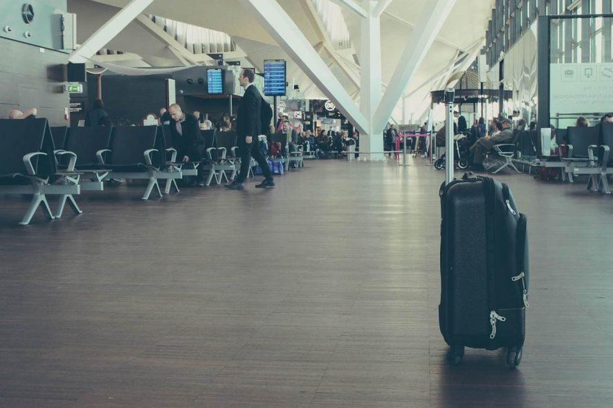Mala de cabine no meio de uma sala de embarque de aeroporto. Foto de Pixabay