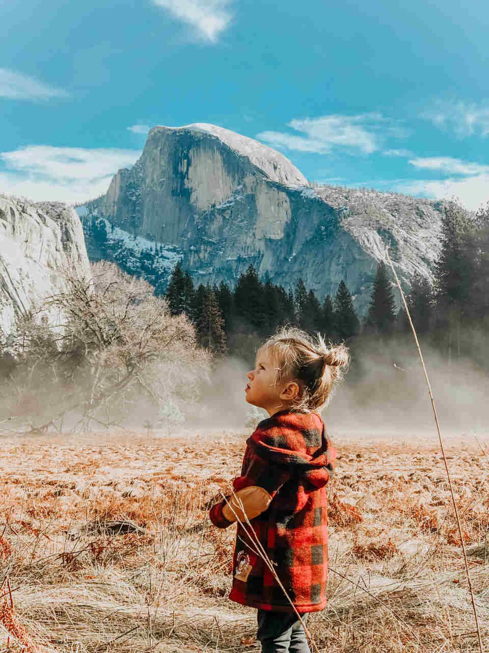 Menina a olhar o céu com uma montanha em fundo