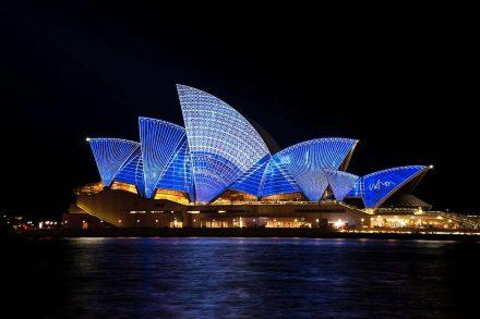 Opera House de Sidney fotografada à noite iluminada de azul. Foto de Pixabay