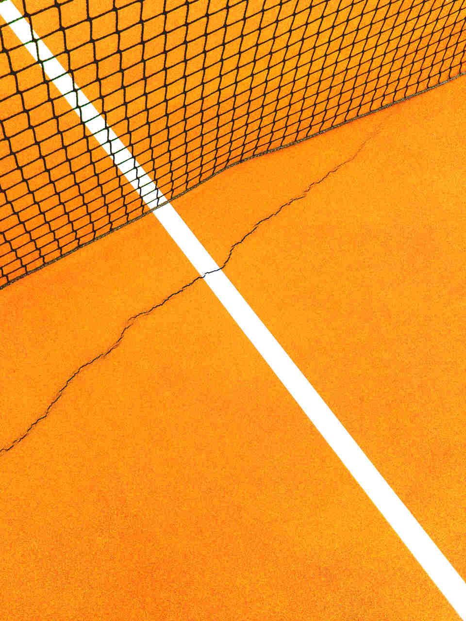 Racha no pavimento de um campo de ténis junto a uma rede