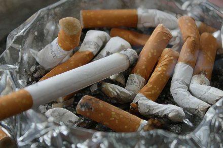 Várias pontas de cigarros apagadas num cinzeiro de vidro com cinza e um cigarro aceso