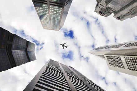 avião em voo por cima de arranha-céus fotografado a partir do solo.
