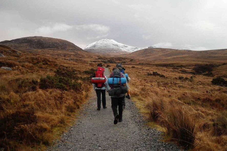 viajantes de mochila às costas a percorrer uma estrada a pé. Foto de Pixabay