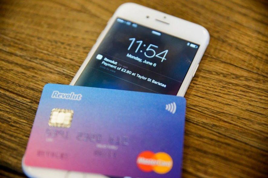 Cartão Revolut em cima de um smartphone com a notificação de um pagamento. Foto de Divulgação