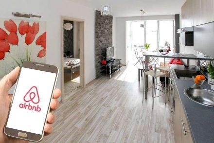 Logotipo do Airbnb no ecrã de um telemovel fotografado dentro de uma sala