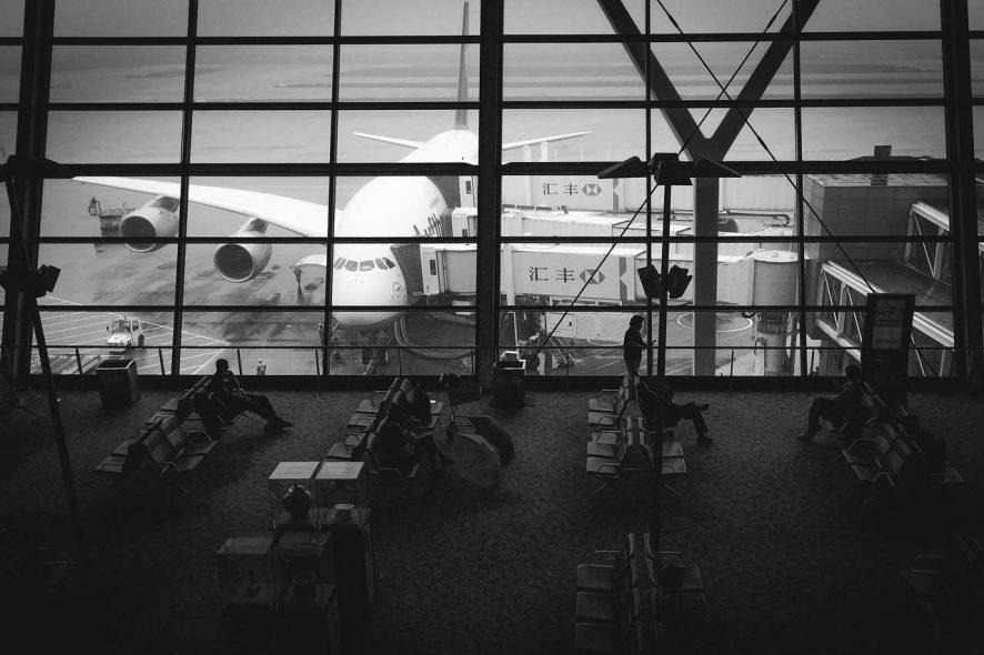 Sala de embarque de aeoporto com avião estacionado no pateo, ligado por duas mangas de embarque. Foto de Pixabay