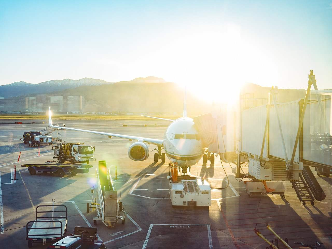 Sol a incidir num avião estacionado no pátio do aeroporto com manga de embarque. Foto de Pixabay