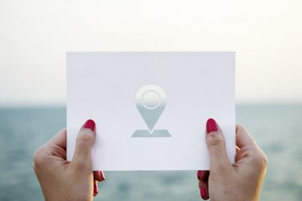 mãos a segurar uma folha com o símbolo do google maps