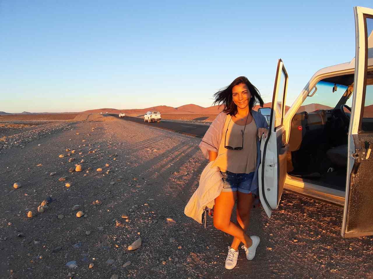 Rita Cerveira Martins junto a um jipe 4x4 parado numa estrada no deserto da Namíbia