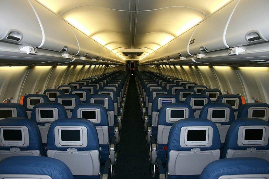 Cabine interior de avião vazia e com vários ecrãs desligados. Foto de Pixabay