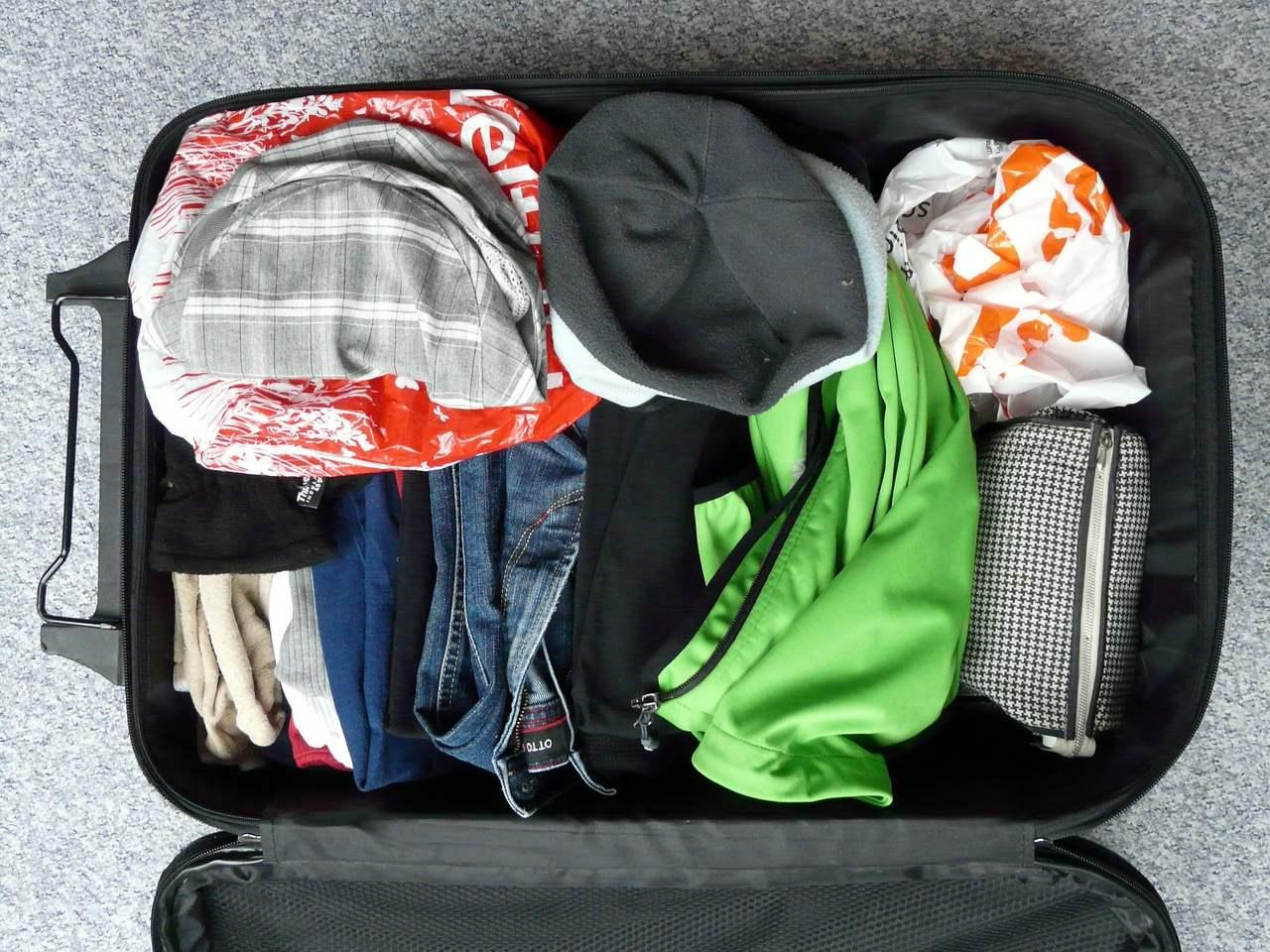 Bagagem de cabine aberta com roupa dentro. Foto de Pixabay