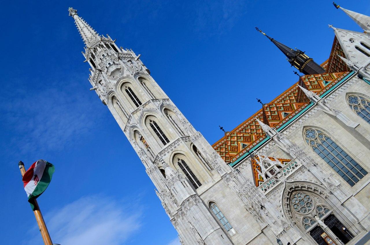 Exterior da Igreja de Santo Estevão em Budapeste ao lado da bandeira da Hungria