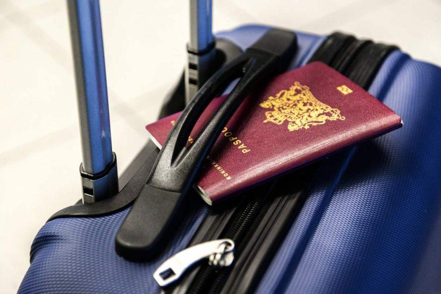 Passaporte em cima de uma mala bagagem de cabine. Foto de Pixabay