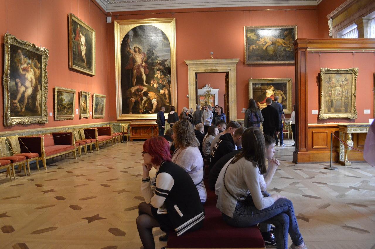 Vários visitantes sentados no interior do Museu Hermitage em São Petresburgo, na Russia