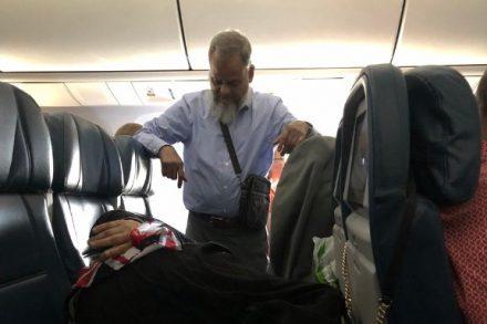 Homem fica de pé no avião para que a mulher possa dormir nos assentos. Foto de Courtney Lee Johnson