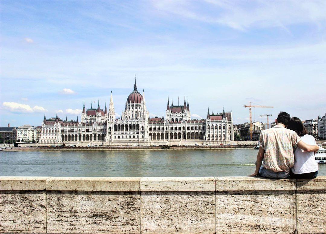 Tiago e Joana do Partir para Ficar sentados às margens do Rio Danúbio com o Parlamento de Budapeste ao fundo